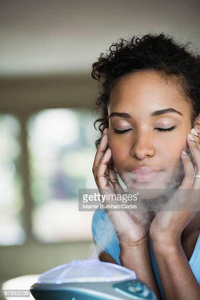 woman sitting by humidifier - humidifier stock pictures, royalty-free photos & images