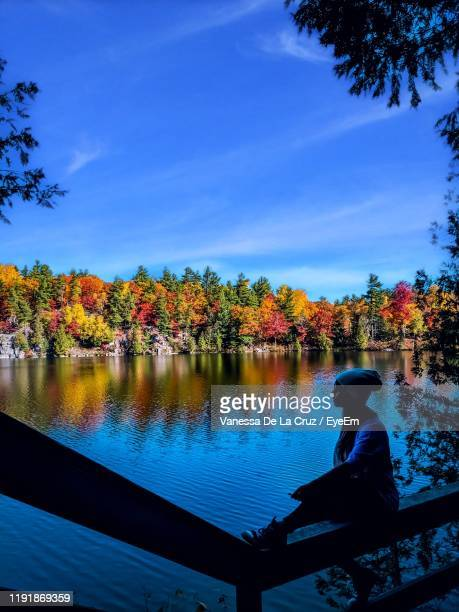 woman sitting by lake against sky during autumn - quebec stock pictures, royalty-free photos & images