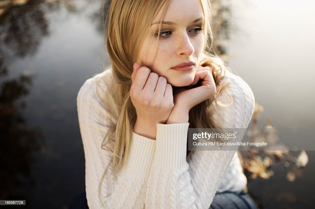 Woman sitting by lake in park : Stock Photo