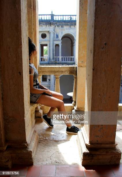 Woman Sitting By Railing In Historic Building