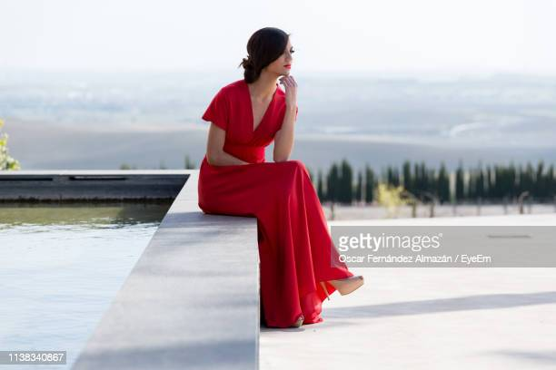 woman sitting by reflecting pool - vestido de noite - fotografias e filmes do acervo