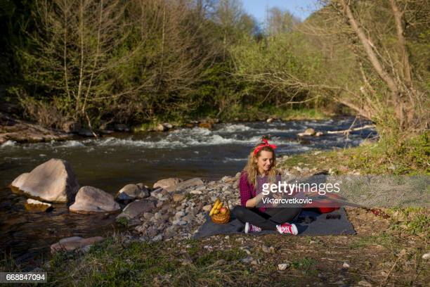 Woman sitting by river and reading a book