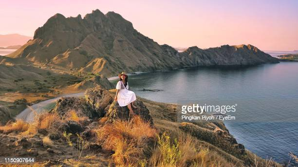 woman sitting by sea on rock - east nusa tenggara stock pictures, royalty-free photos & images