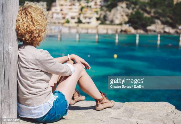 Woman Sitting By Sea