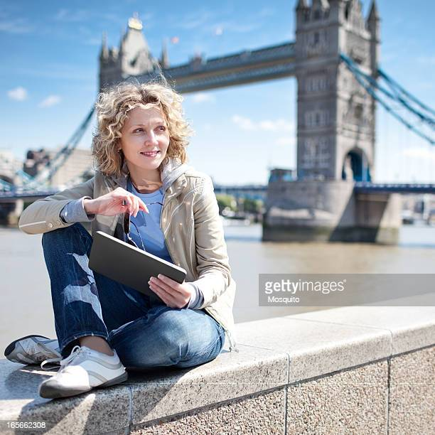 Woman sitting by the river using a tablet