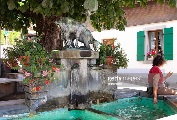 woman sitting by village fountain with hand in water - vaud canton stock pictures, royalty-free photos & images