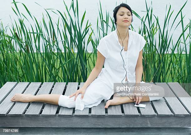 woman sitting by water, listening to mp3 player - short sleeved stock pictures, royalty-free photos & images