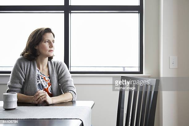 Woman sitting by window looking into the distance