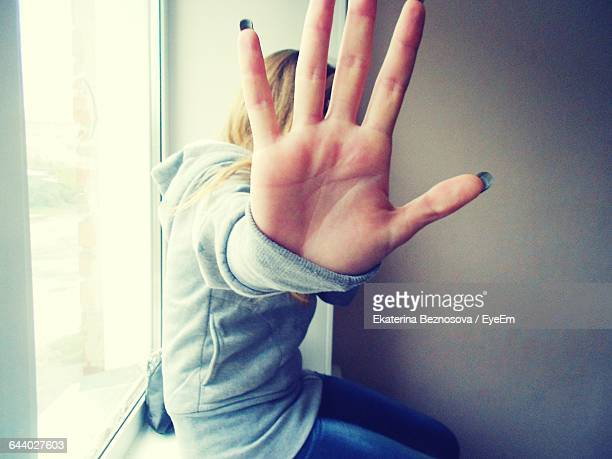 Woman Sitting By Window Making Stop Gesture
