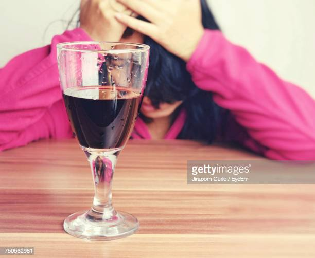 woman sitting by wineglass at wooden table - hangover stock photos and pictures