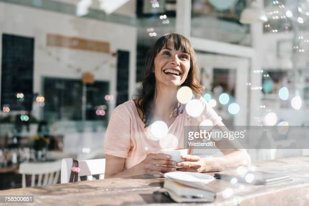 Woman sitting cafe, watching soap bubbles