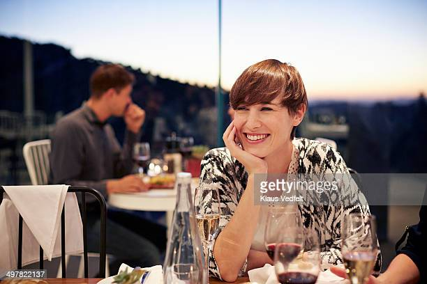 Woman sitting casual & laughing at dinner