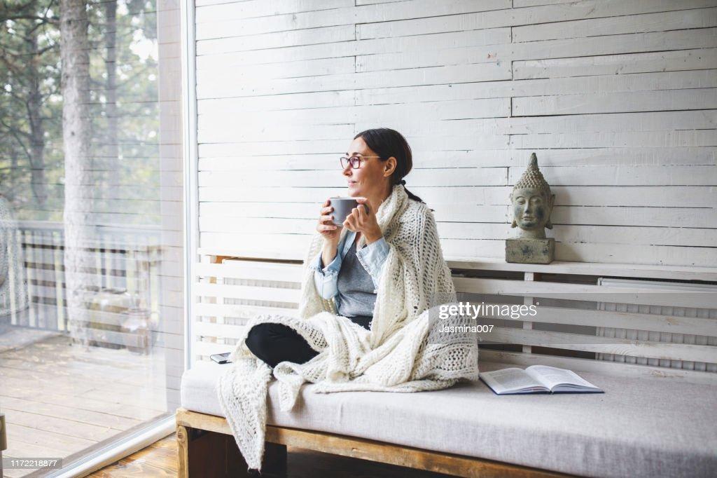 Femme s'asseyant confortablement et regardant par la fenêtre : Photo
