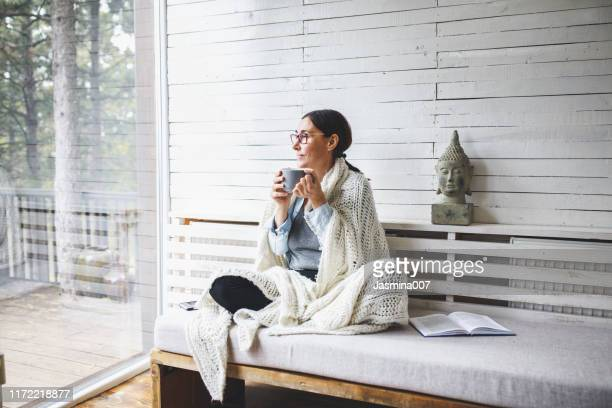 woman sitting comfortable and looking through the window - serene people stock pictures, royalty-free photos & images