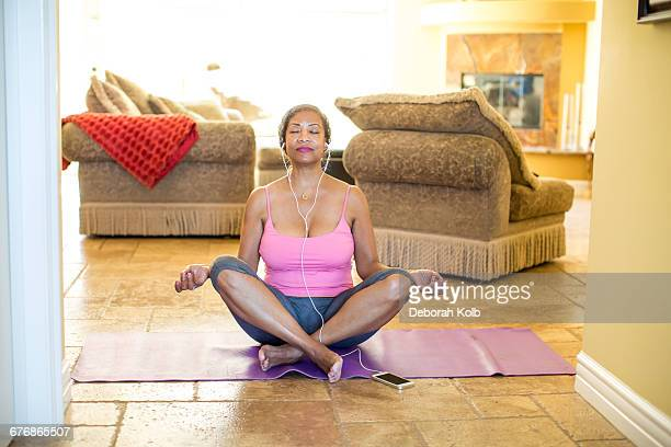 woman sitting cross legged meditating - yoga pants stock photos and pictures