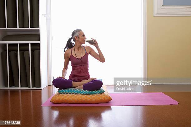 woman sitting cross legged on cushion drinking water - one mature woman only stock pictures, royalty-free photos & images