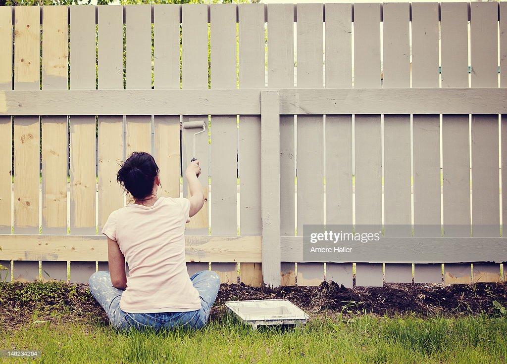 Woman sitting cross legged painting a fence : Stock Photo