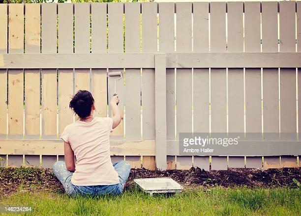 Woman sitting cross legged painting a fence