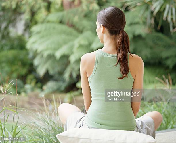 woman sitting crossed legged on cushion, outdoors, rear view - three quarter length stock pictures, royalty-free photos & images