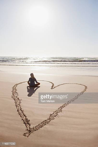 woman sitting cross-legged in heart on beach - liefde stockfoto's en -beelden
