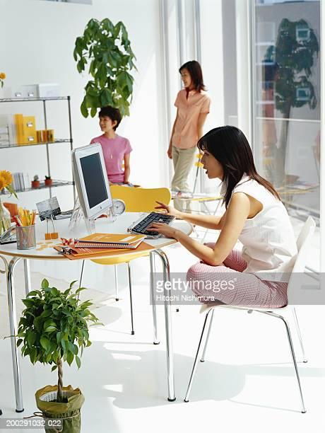 Woman sitting cross-legged on chair, using computer