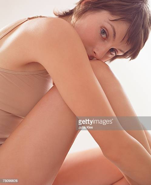 woman sitting curled up with chin on knee - halbbekleidet stock-fotos und bilder