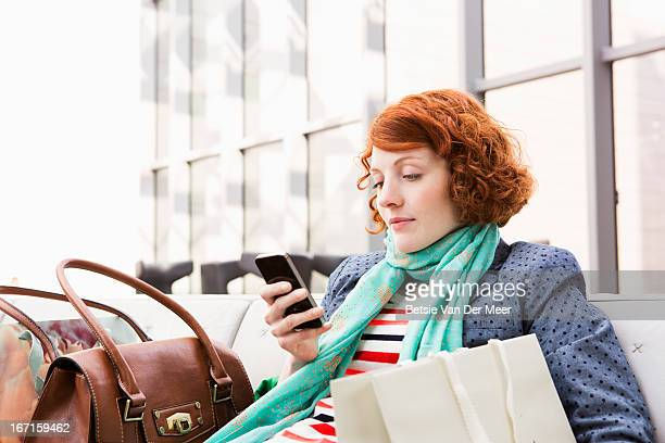 woman sitting down checking messages. - one young woman only stock pictures, royalty-free photos & images