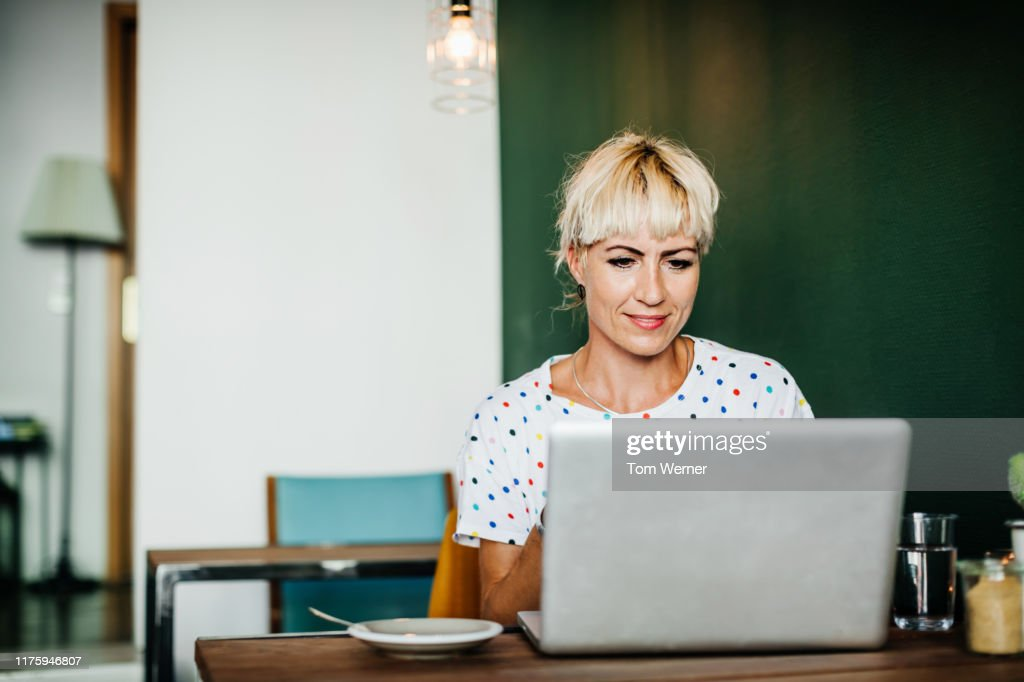 Woman Sitting Down In Cafe Using Lapotop : Stock-Foto