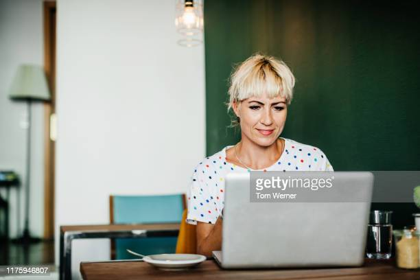 woman sitting down in cafe using lapotop - mid adult women stock pictures, royalty-free photos & images