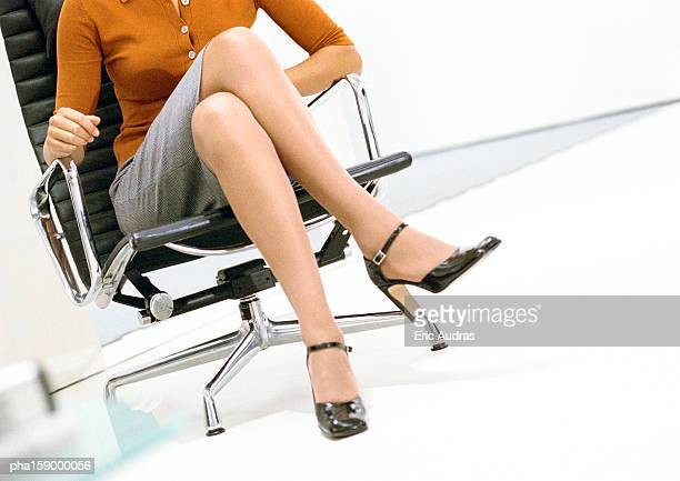 Woman sitting down, low section.