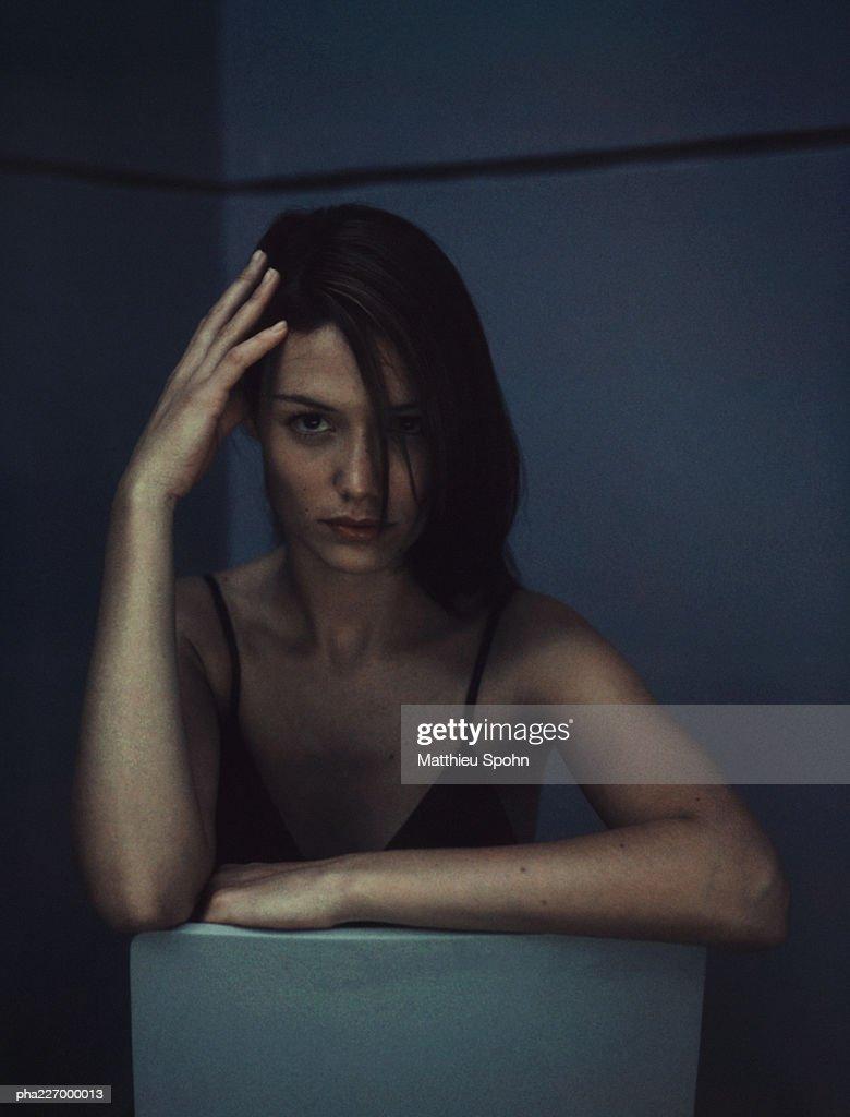 Woman sitting, fingers on head, looking into camera, portrait. : Stockfoto