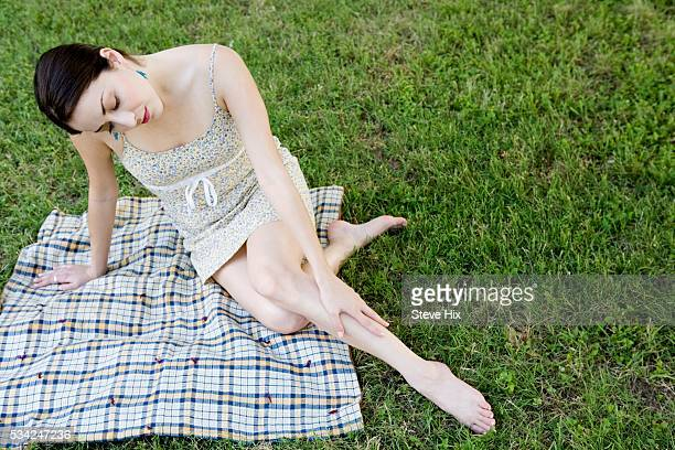woman sitting grass on a blanket - bow legs stock photos and pictures
