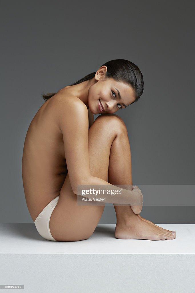 Woman sitting half naked smiling, grey background : Stock Photo