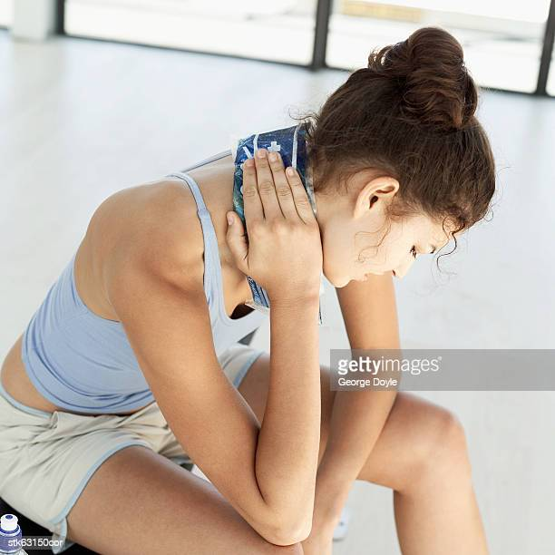 woman sitting holding a cold pack on her neck