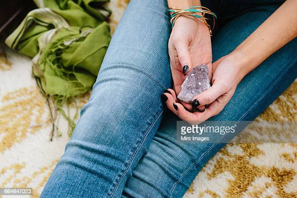 a woman sitting holding a small purple crystal in her hands. - amethyst stock photos and pictures