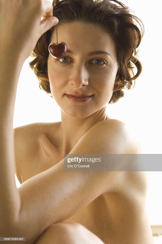 Woman sitting, holding cherry, naked, portrait. : Stock Photo