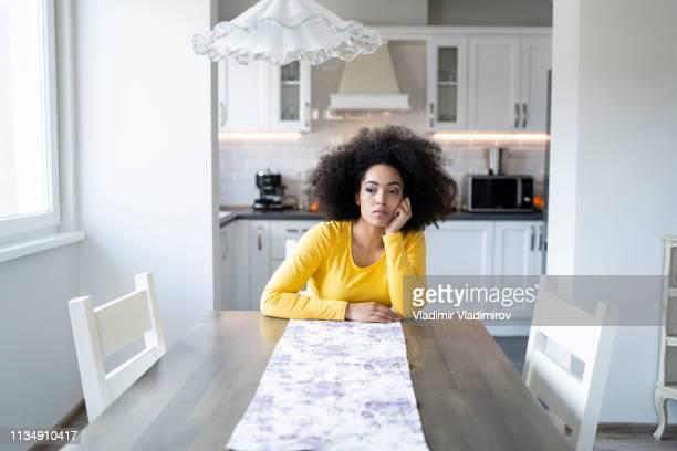 woman sitting home alone - domenica foto e immagini stock