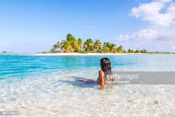 woman sitting in a blue lagoon in front of tropical island - perfection stock pictures, royalty-free photos & images
