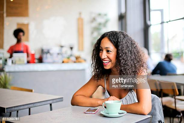 woman sitting in a cafe - mid adult women stock pictures, royalty-free photos & images