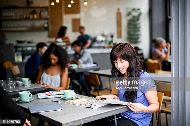woman sitting in a cafe reading a magazine - magazine stock pictures, royalty-free photos & images