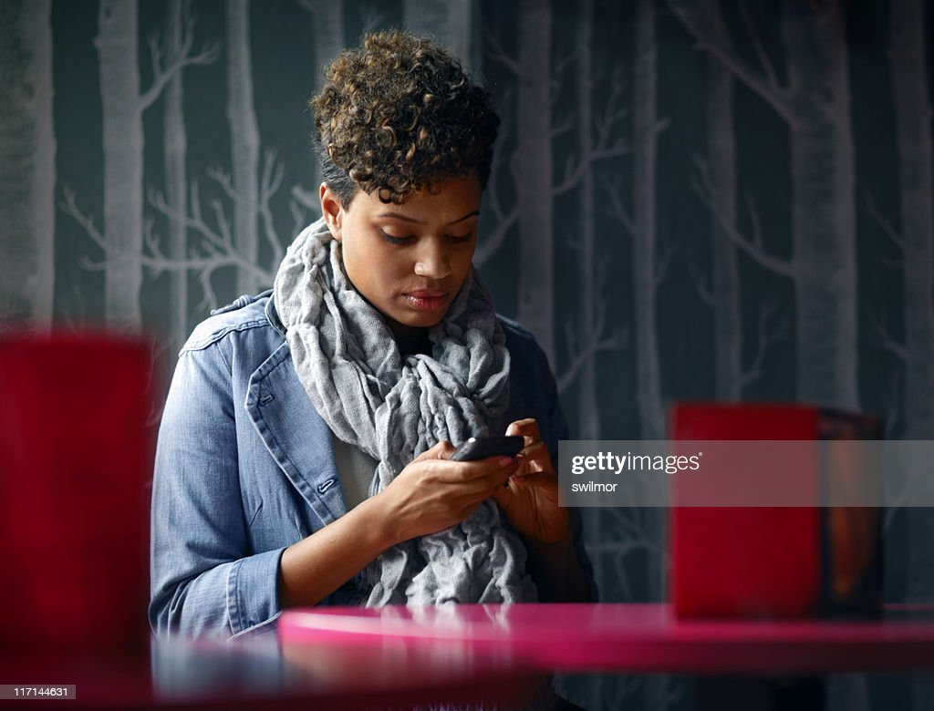 Woman Sitting in a Cafe Texting : Stock Photo
