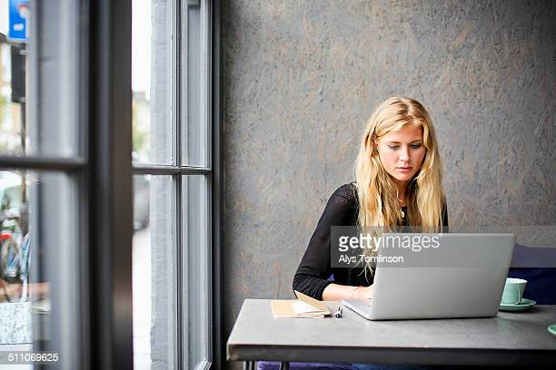 woman sitting in a cafe using a laptop computer - using laptop stock pictures, royalty-free photos & images