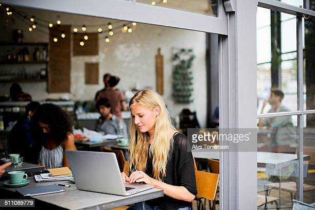 woman sitting in a cafe using a laptop computer - incidental people stock pictures, royalty-free photos & images