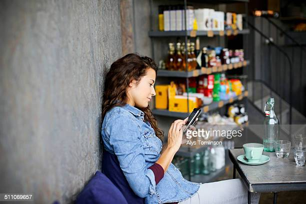Woman Sitting in a Cafe Using a Smartphone