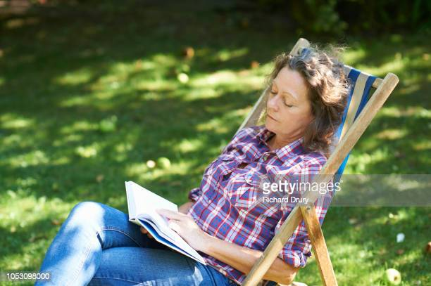 Woman sitting in a deckchair relaxing in the garden