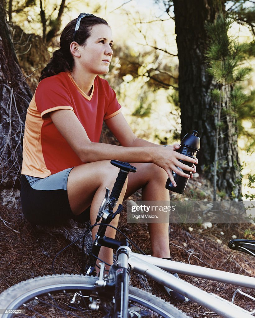 Woman Sitting in a Forest With Her Mountain Bike by Her Side : Stock Photo