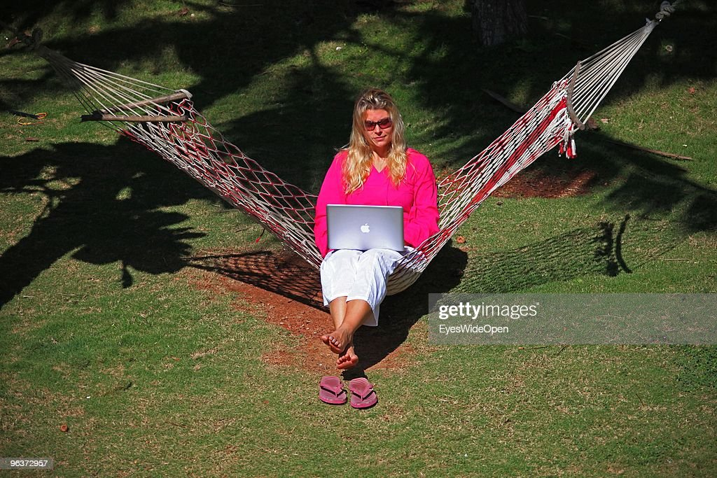 Woman sitting in a hammock and working with a notebook on January 12, 2010 in Varkala near Trivandrum, Kerala, India.