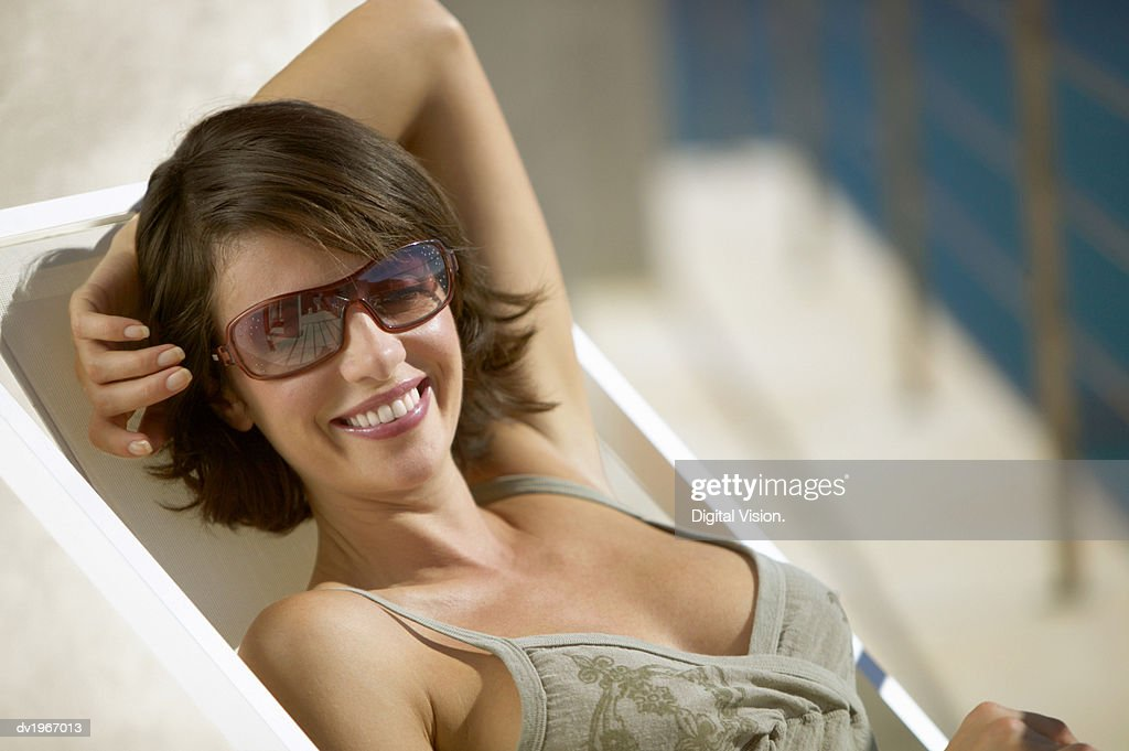 Woman Sitting in a Lounger Wearing Sunglasses : Stock Photo