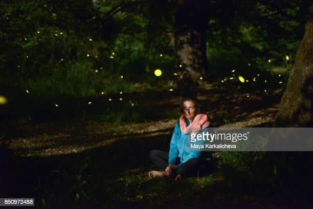 woman sitting in a night woodland with fireflies around, zagoria / epirus, greece - glowworm stock pictures, royalty-free photos & images