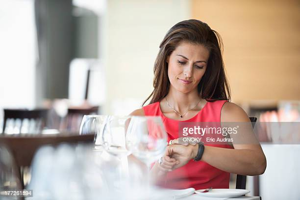 Woman sitting in a restaurant and looking at wristwatch